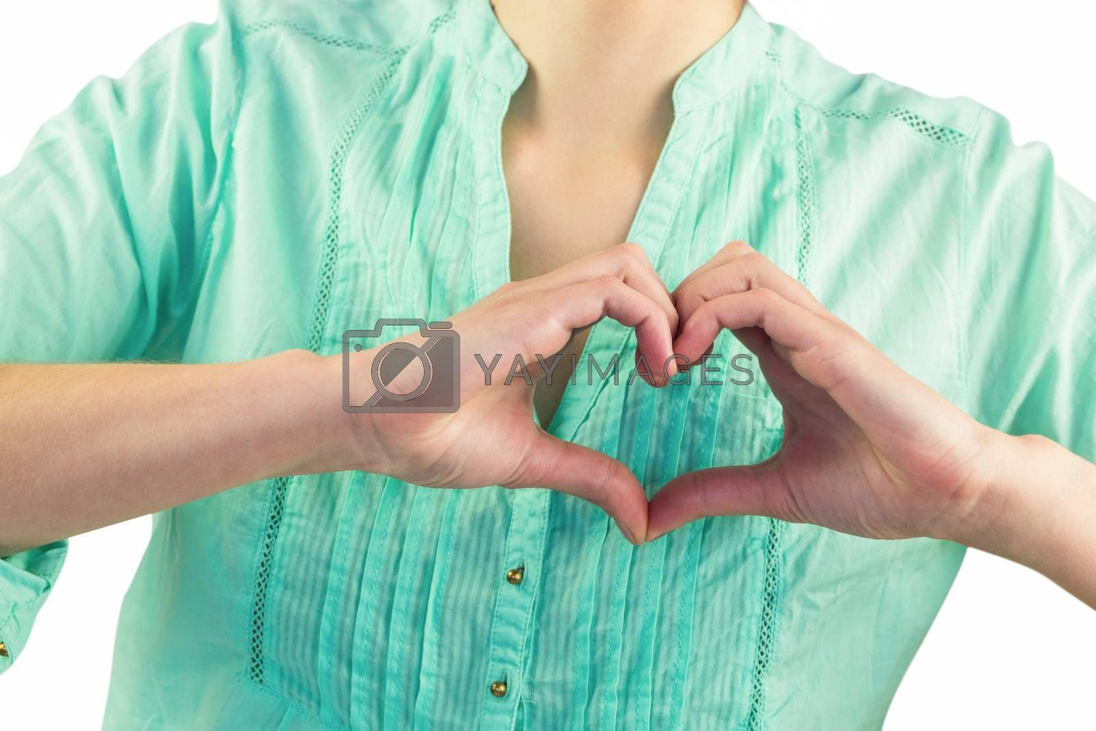 Mid section of woman making heart shape of fingers against white background