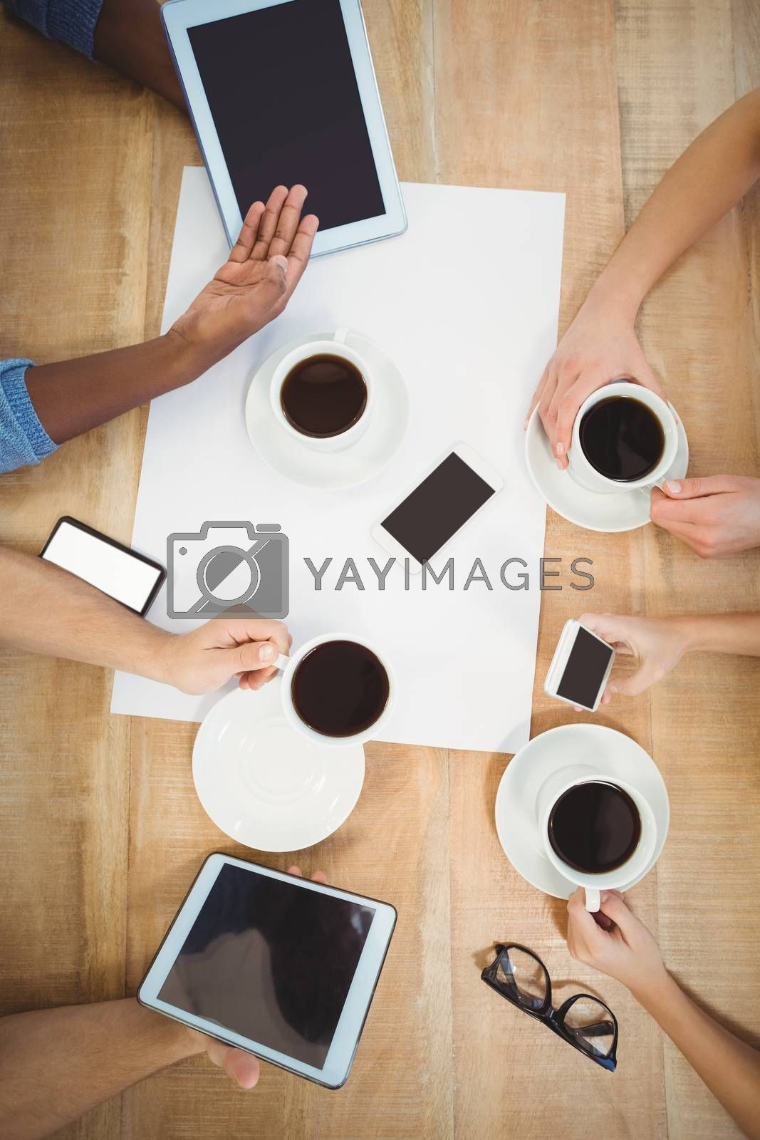 Overhead view of people using technology with person showing digital tablet at desk in office