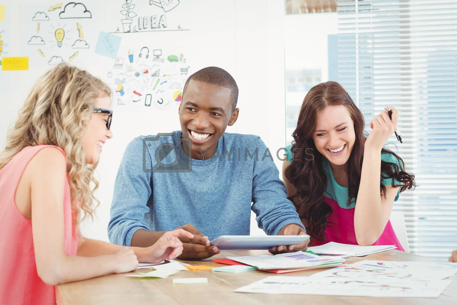 Smiling business professionals using digital tablet at desk in creative office