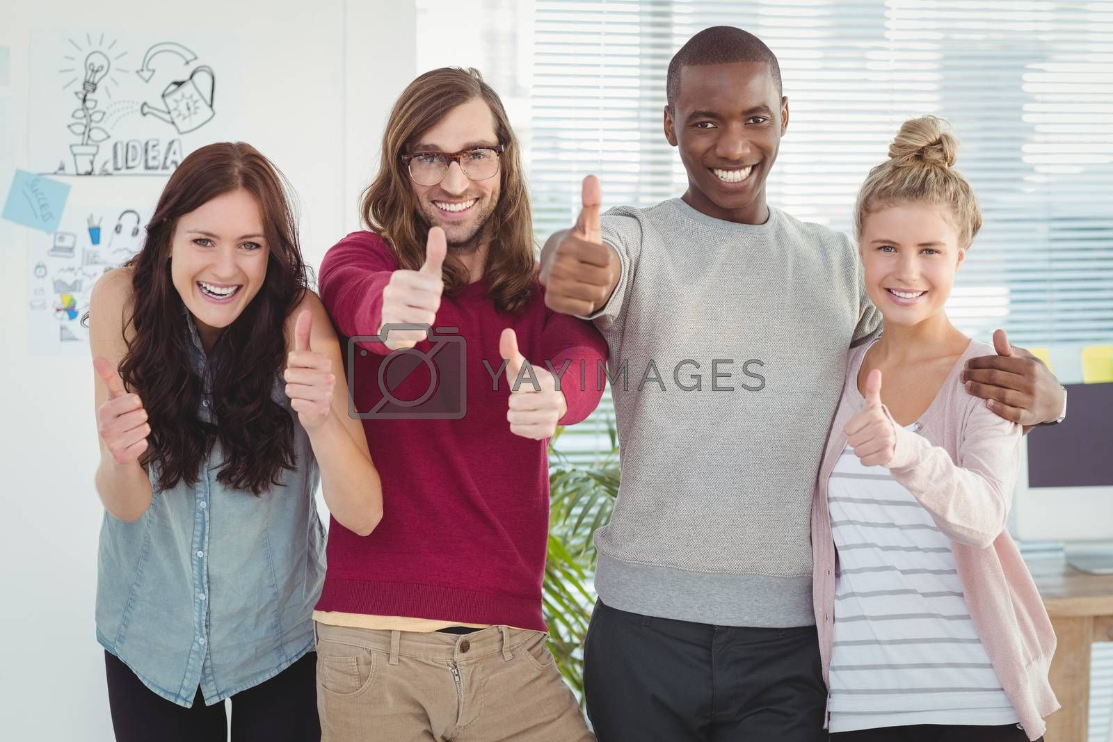 Portrait of smiling business team with thumbs up at office