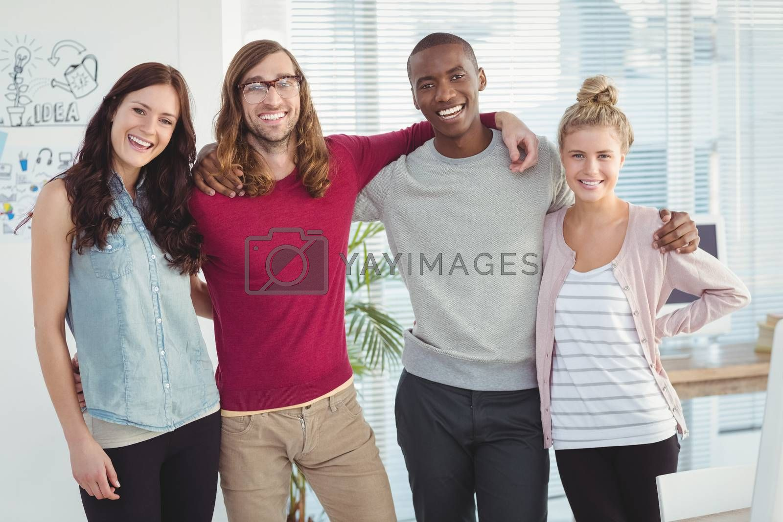 Portrait of smiling business team with arms around at office
