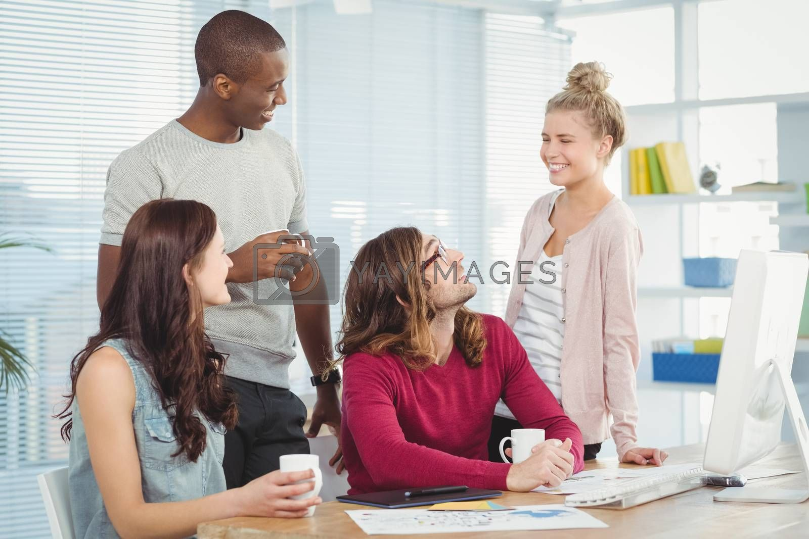 Smiling business team at computer desk in office