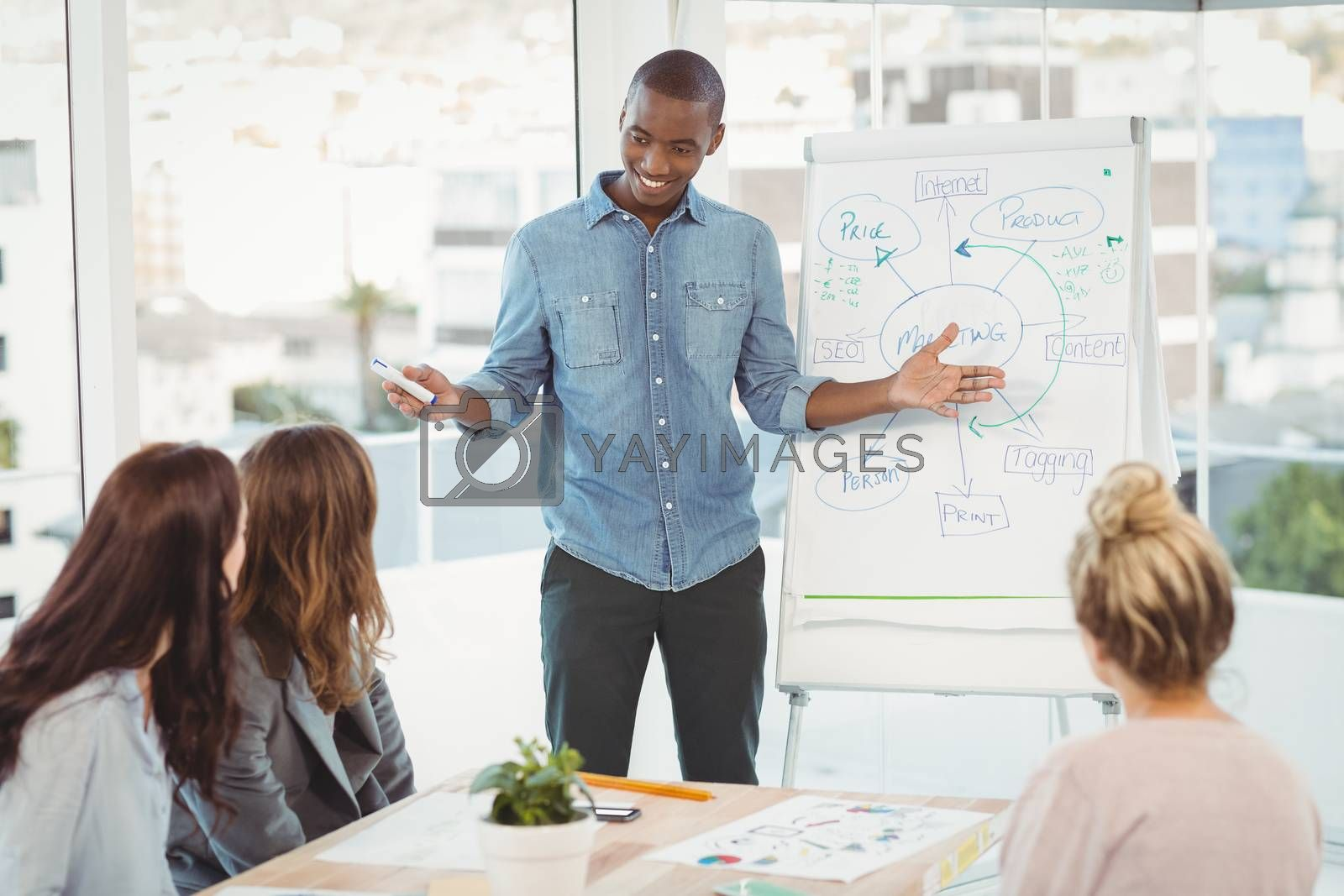 Man gesturing by white board while discussing with coworkers at office