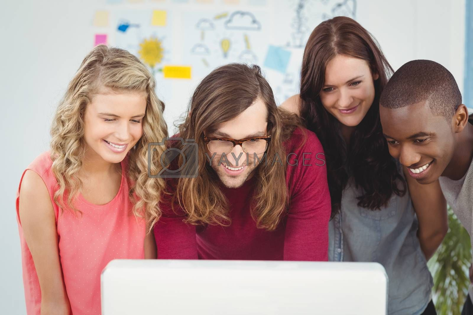 Smiling business team looking at computer while working at creative office