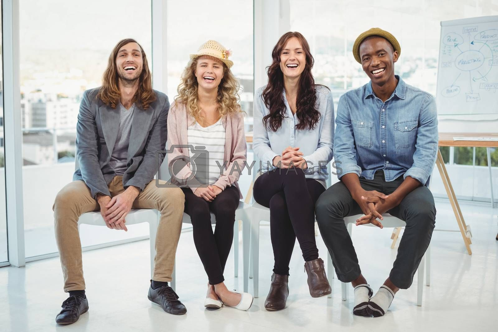 Full length portrait of happy business people sitting on chair in office