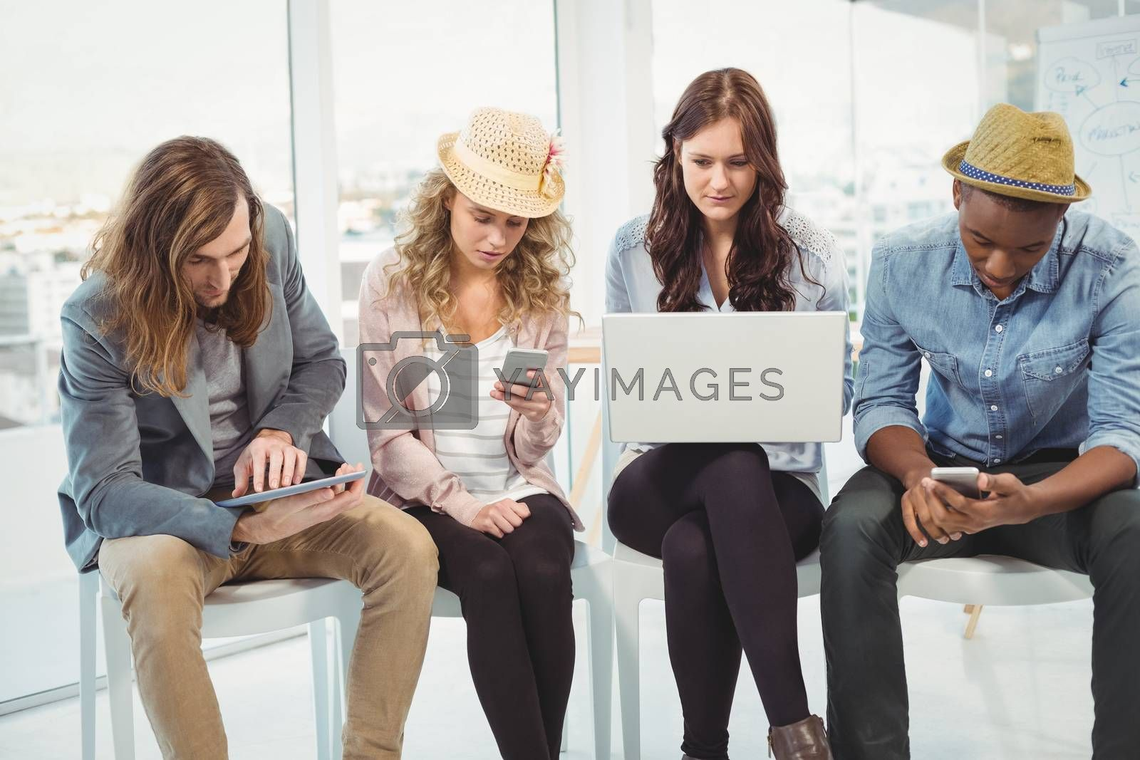 Business people using technology while sitting on chair in creative office