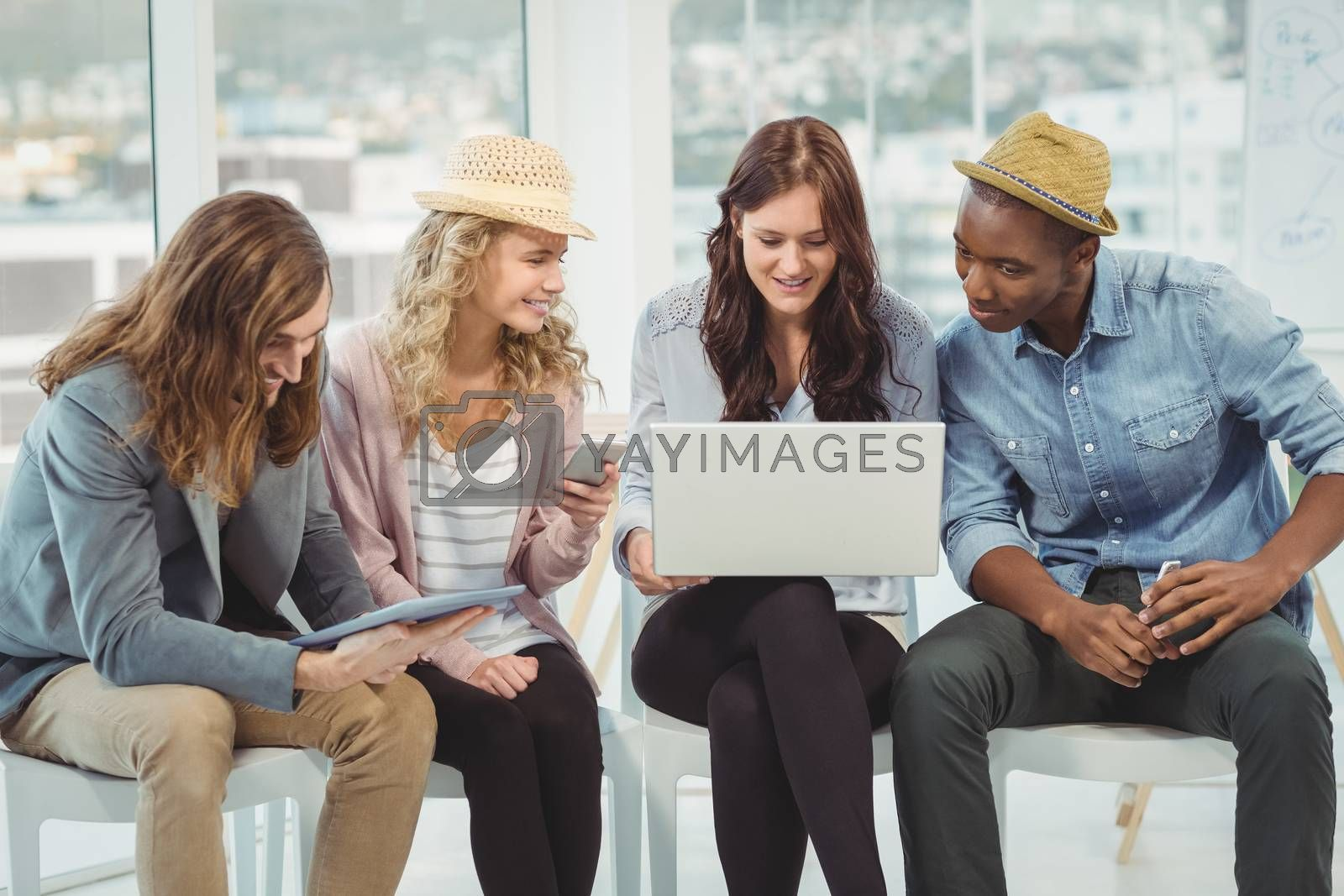 Smiling business people using technology while discussing in creative office