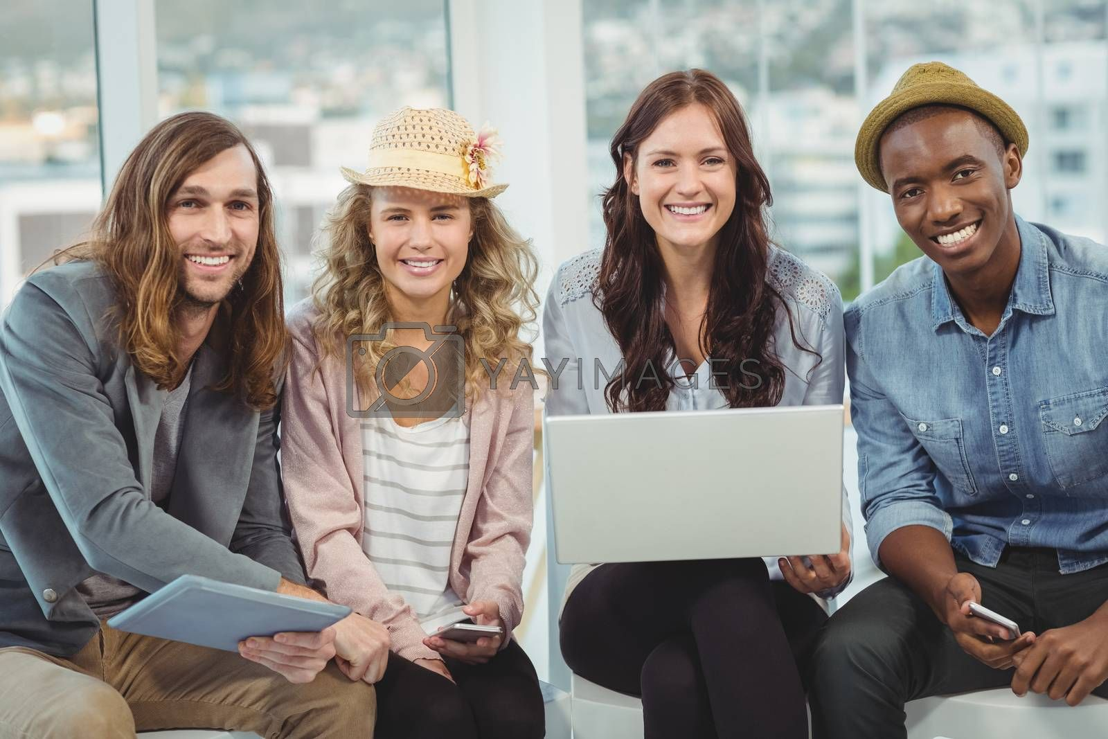 Portrait of smiling business people with laptop and digital tablet while sitting on chair in office