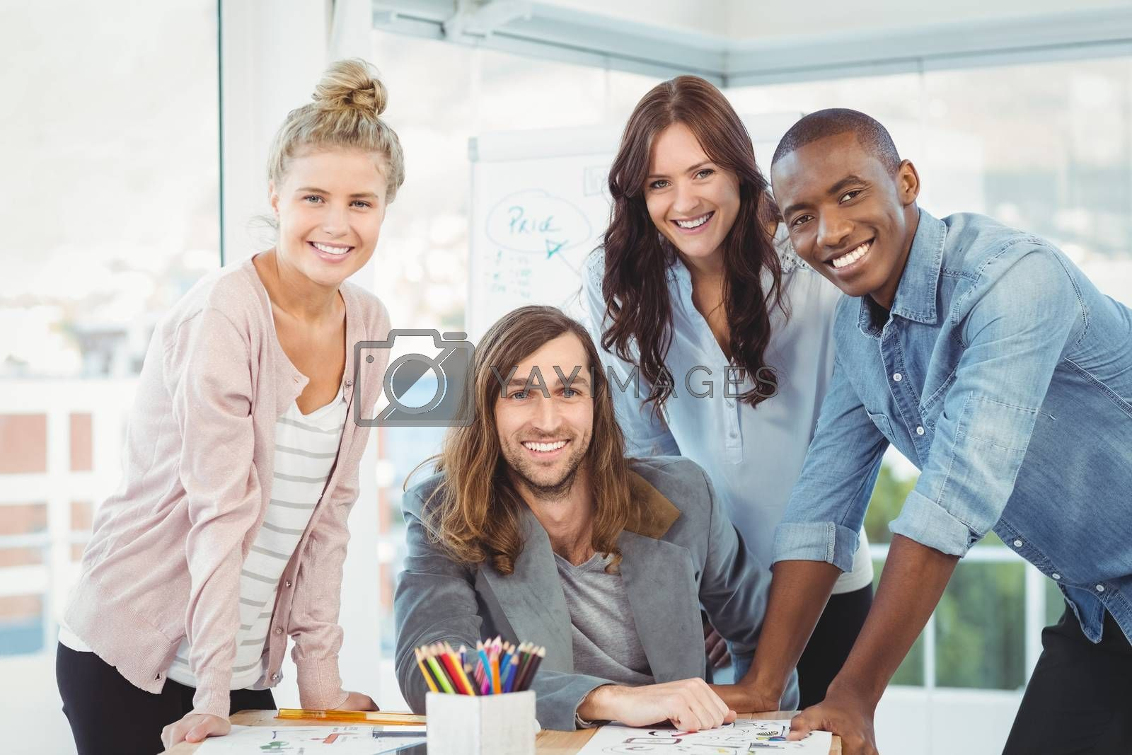 Portrait of happy business team discussing at desk in creative office