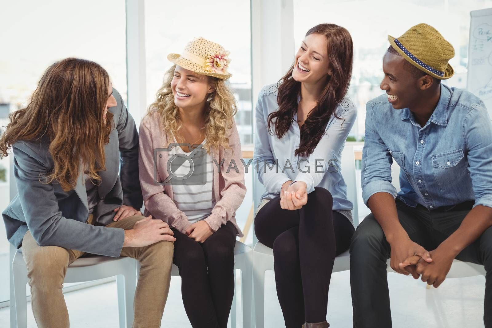 Happy business people sitting on chair in office