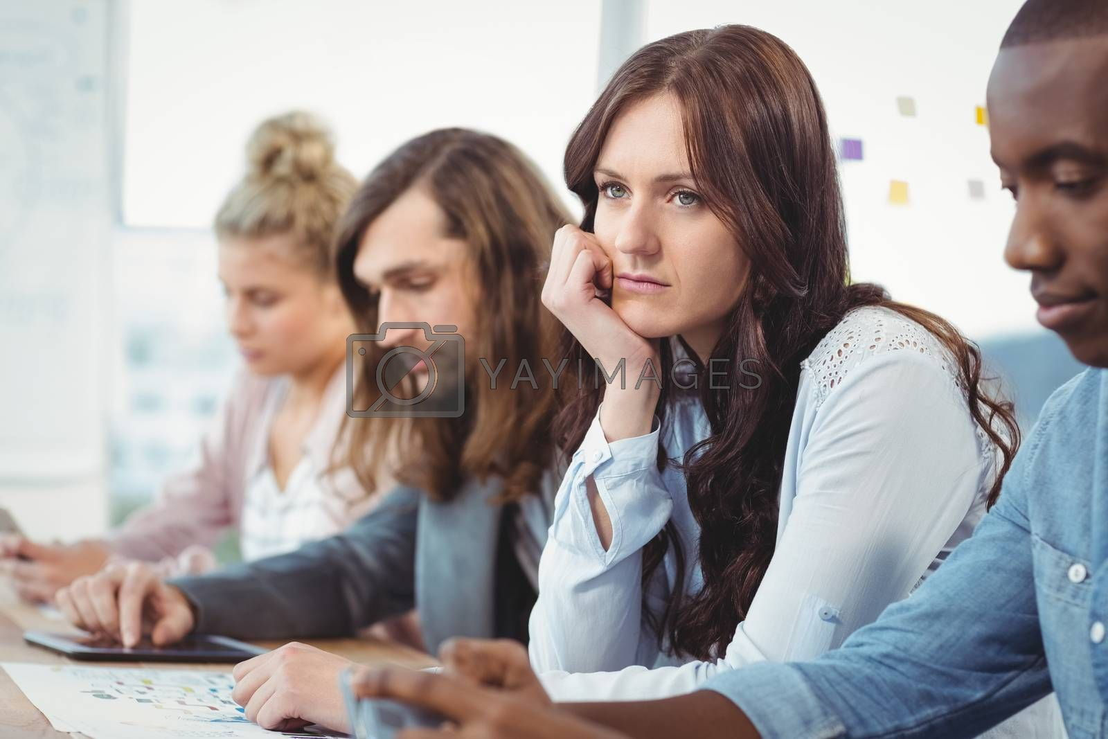 Thoughtful woman sitting at desk with coworkers in office