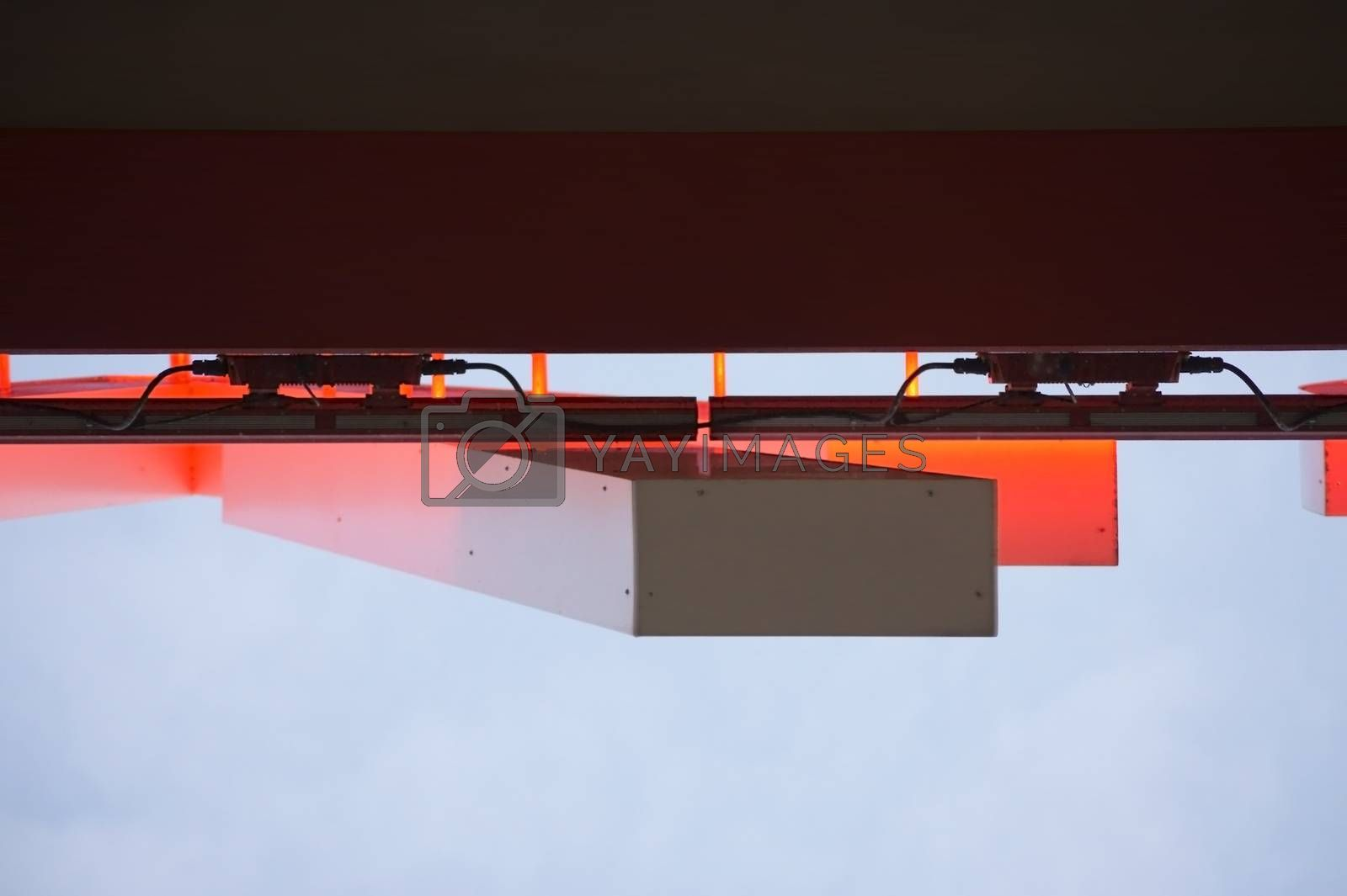 The bottom view and a detail of an illuminated red neon sign.