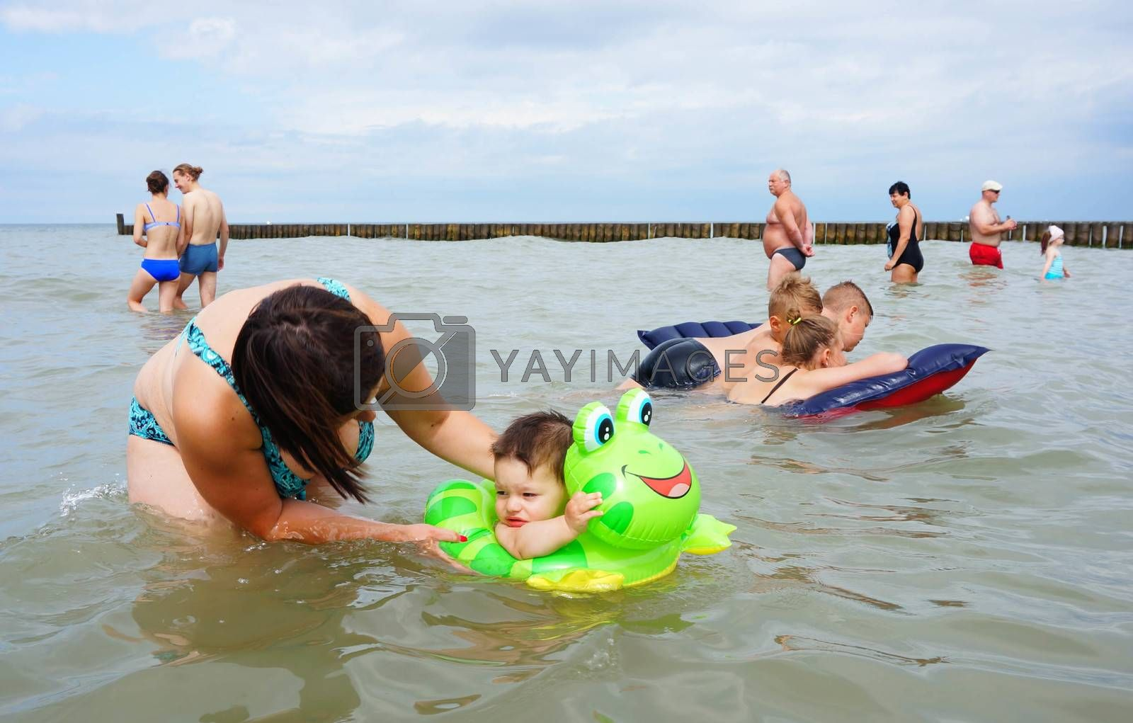 SIANOZETY, POLAND - JULY 21, 2015: Adults and children playing in the water at a beach