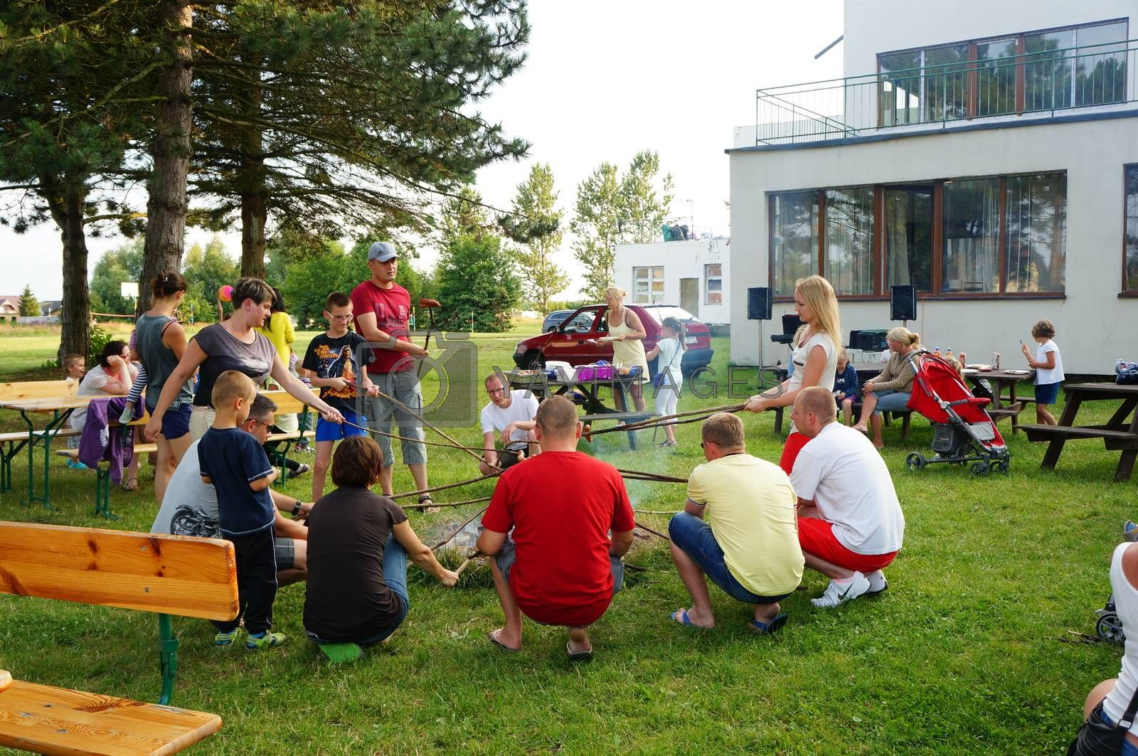 SIANOZETY, POLAND - JULY 22, 2015: People sitting around a fire place and grilling sausages at a barbecue event