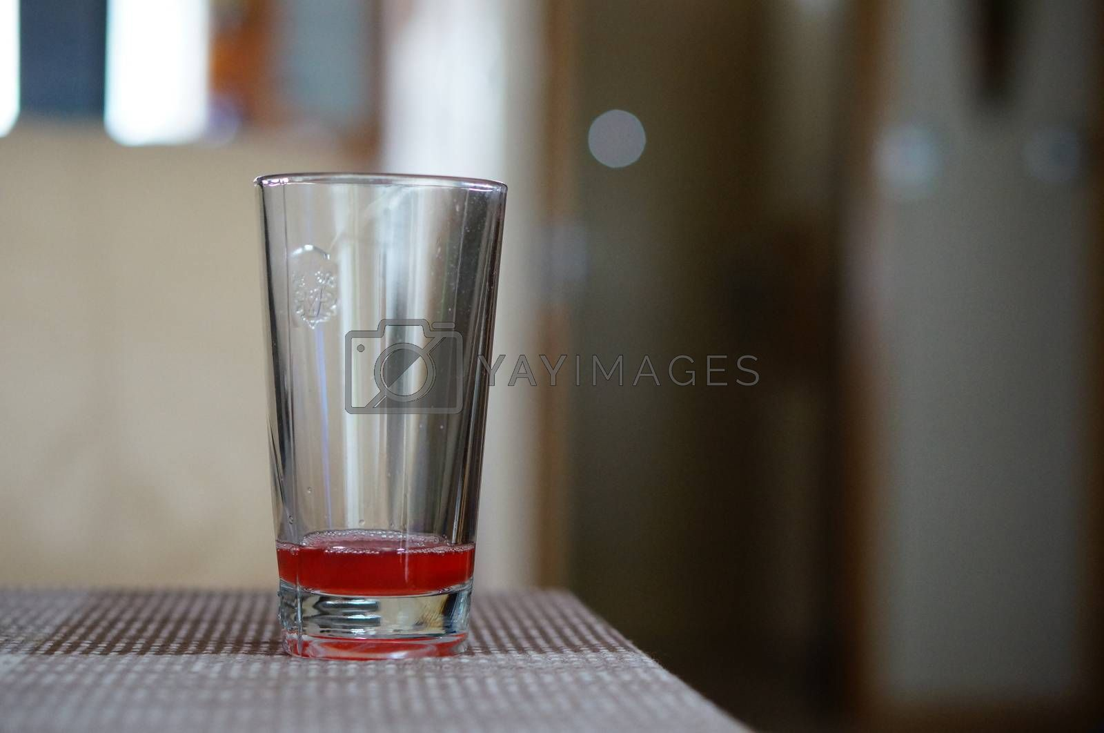 Almost empty glass with juice standing on table