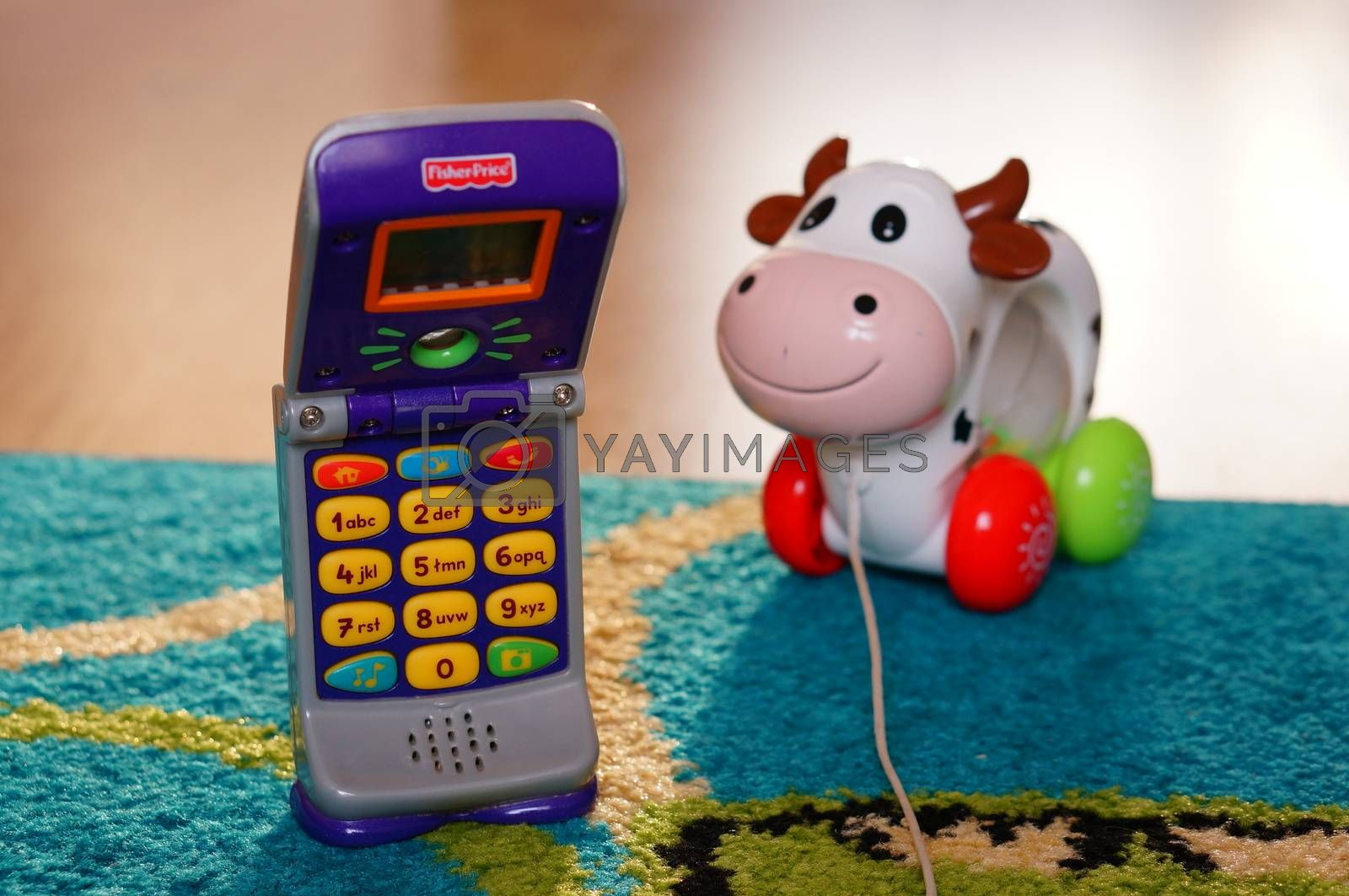 POZNAN, POLAND - AUGUST 20, 2015: Fisher Price plastic toy phone and toy cow in background
