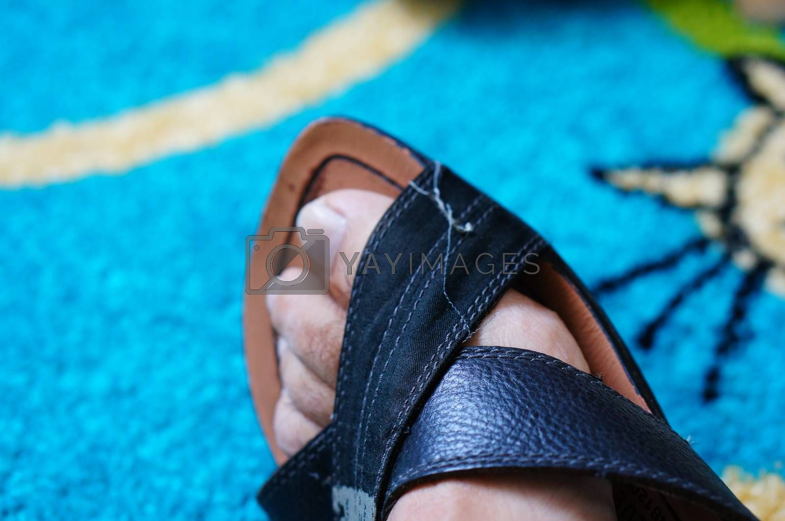 Foot in leather sandal on blue carpet