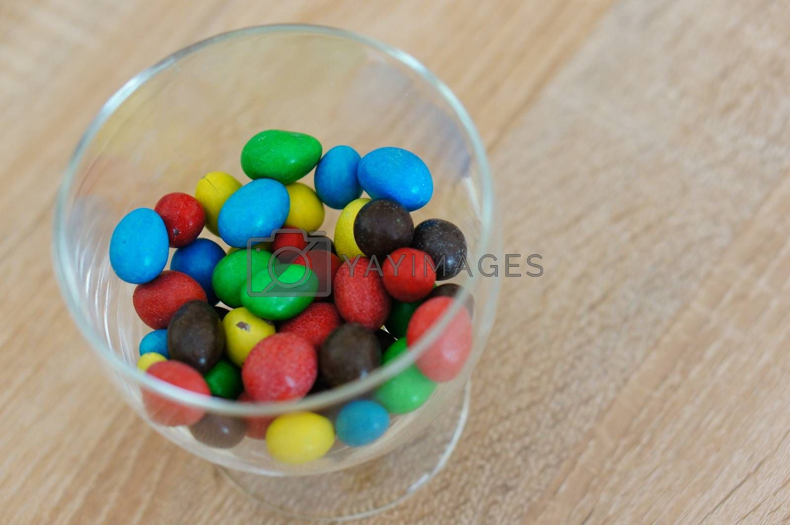 Colorful chocolate peanuts in glass