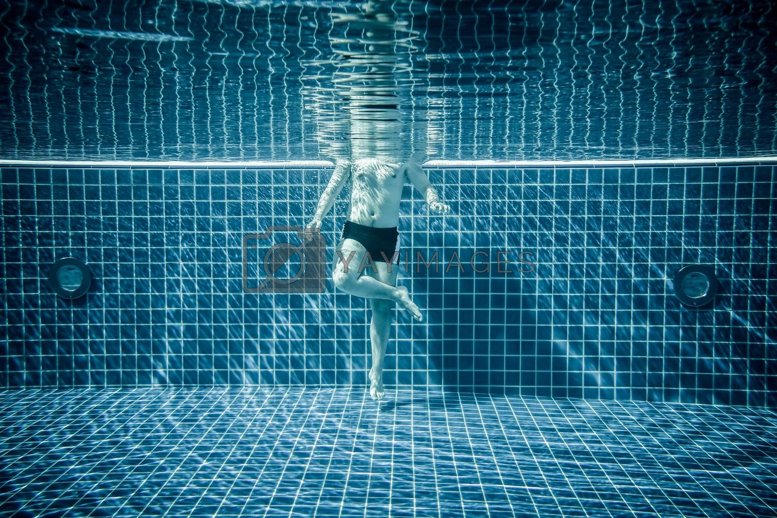 Man standing under water in a swimming pool