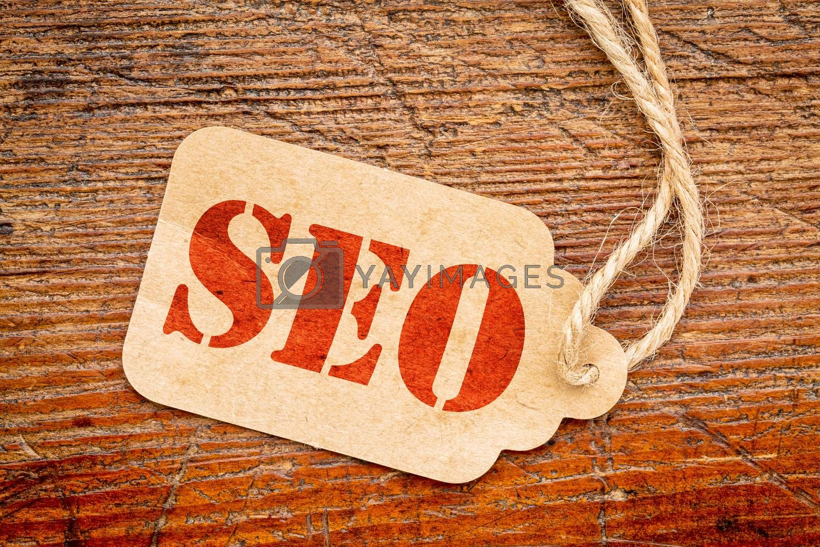 SEO - search engine optimization acronym on a paper price against rustic wood