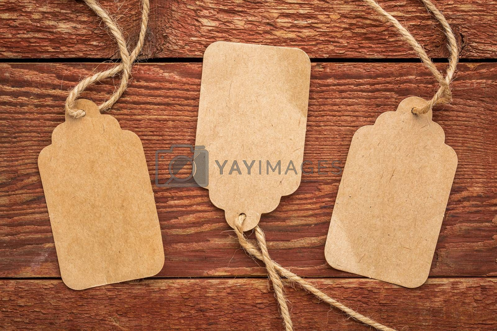 three blank paper price tags with a twine against planks of rustic barn wood