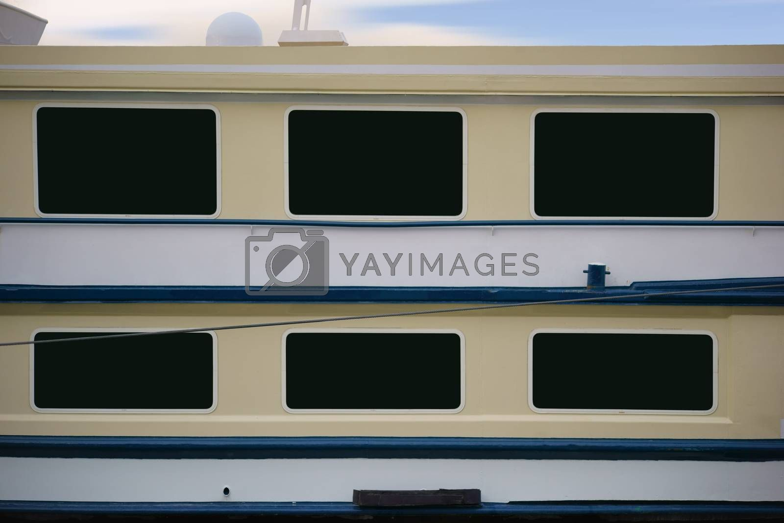The side view of a passenger ship, starboard, with windows and railing.