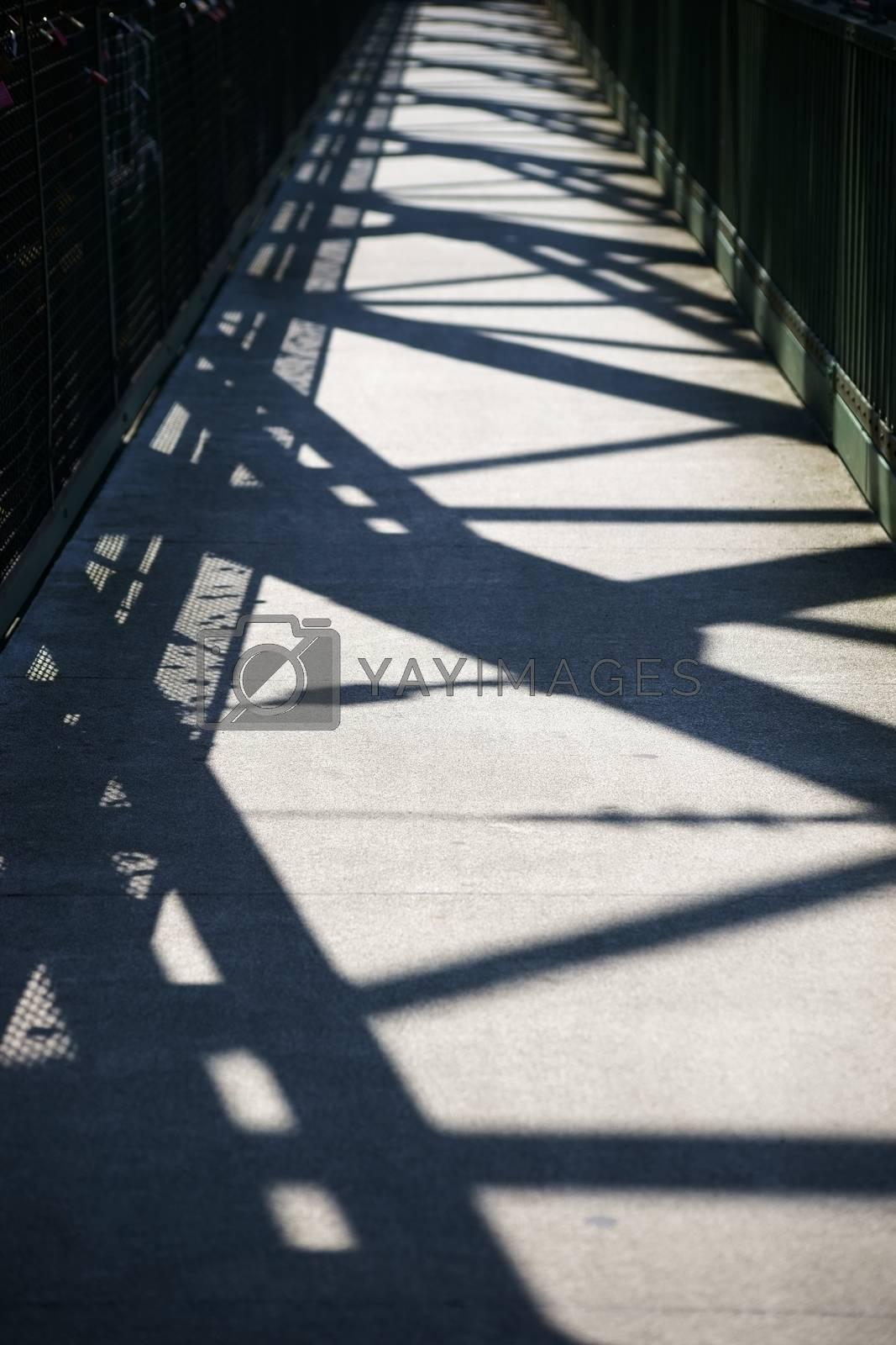 A bridge railing and a bridge construction cast a abstract shadow.