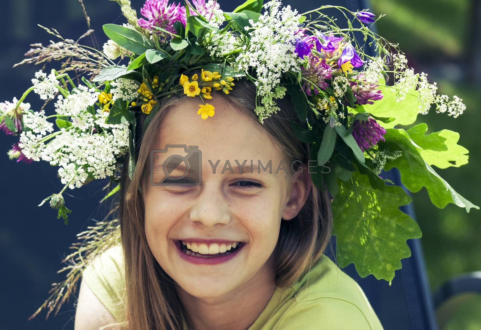 Portrait of happy smiling young girl with flower wreath on her head on sunny summer day. Cross processing effect added