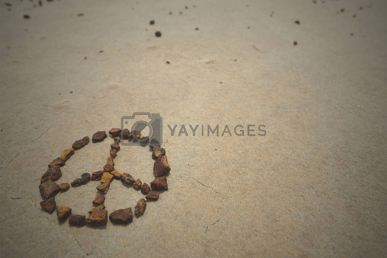 Peace symbol made with rocks on beach sand. Summer hipster background.
