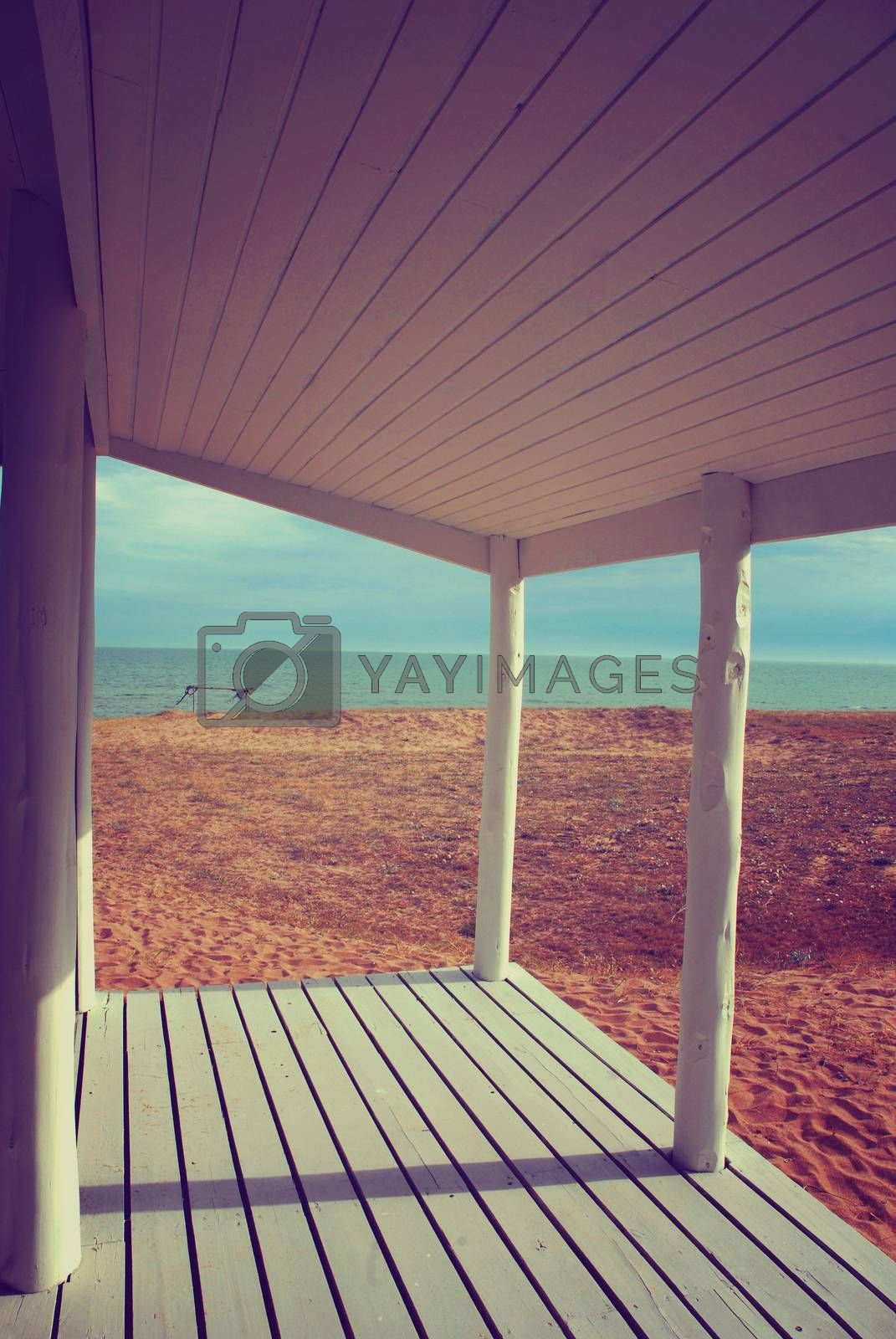 White beach house porch with vintage style filter effect and ocean view background.