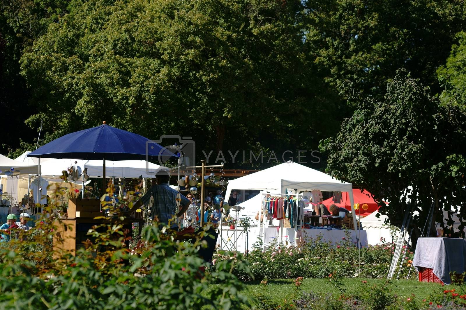 Mainz, Germany - August 29, 2015: Small stalls and tents of the artist market surrounded by trees and flowerbeds on the Mainz Wine Market in the city park and rose garden on August 29, 2015 Mainz.