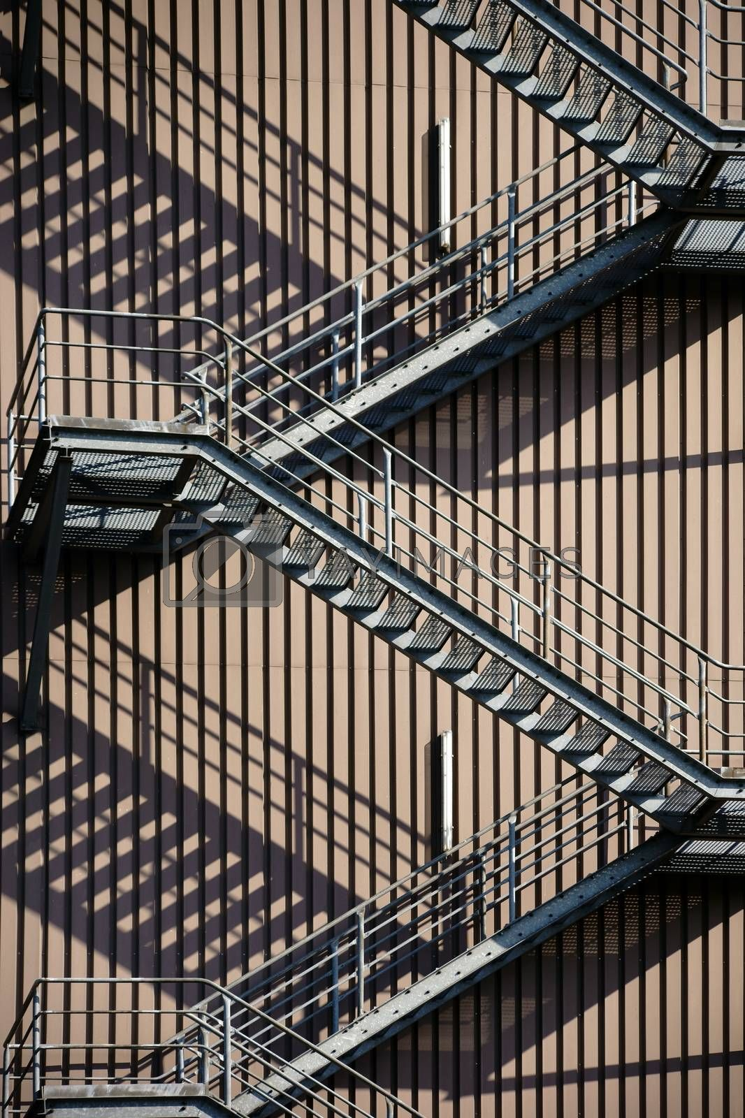 A walk outside stairway at an industrial building casts a shadow.