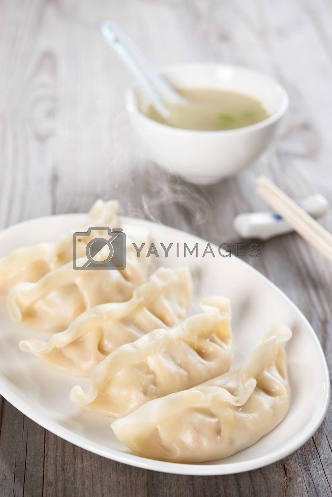 Fresh dumpling on plate with soup. Chinese food on old wooden background.