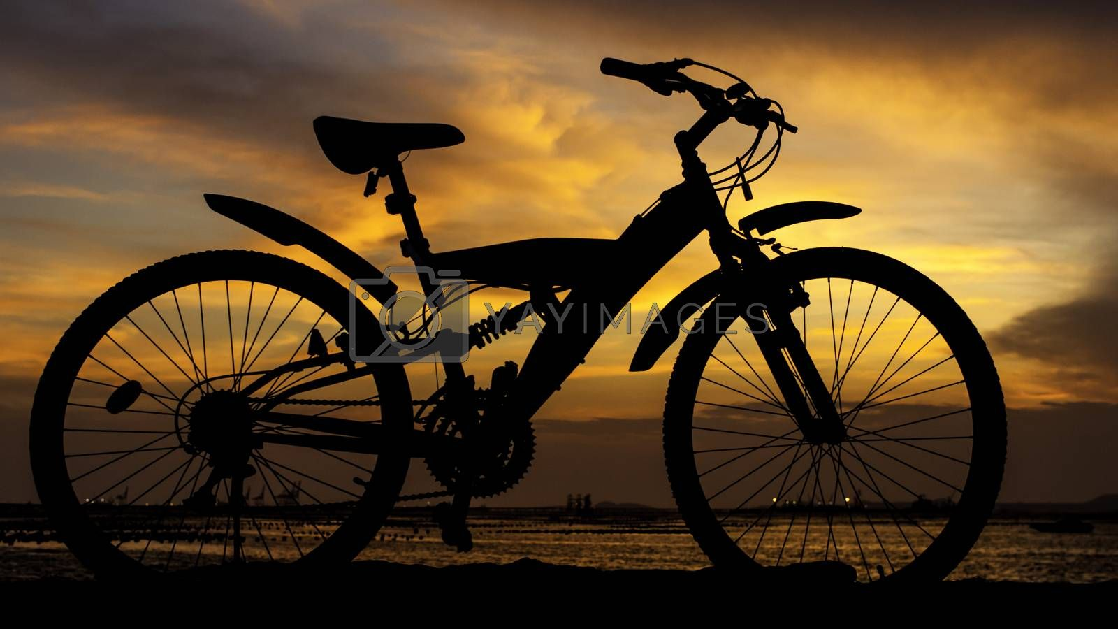 Silhouette of mountain bike with sunset sky beside sea, Thailand