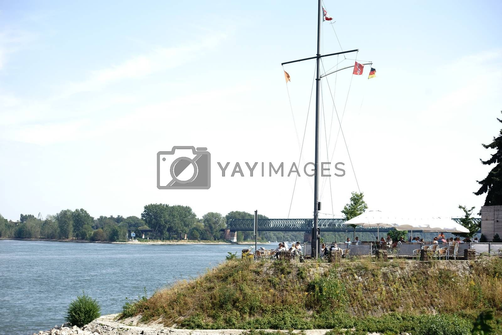 Mainz, Germany - August 22, 2015: A beer garden on the banks of the river Rhine and on the Victor Hugo shore with guests on August 22, 2015 in Mainz.