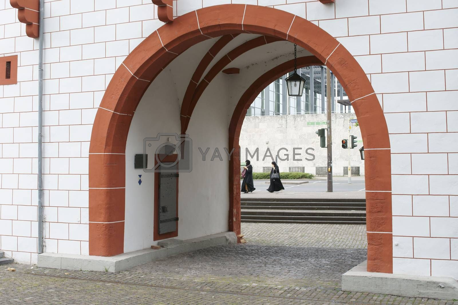 Two women in burka crossing a street behind an archway of the iron tower in Mainz.