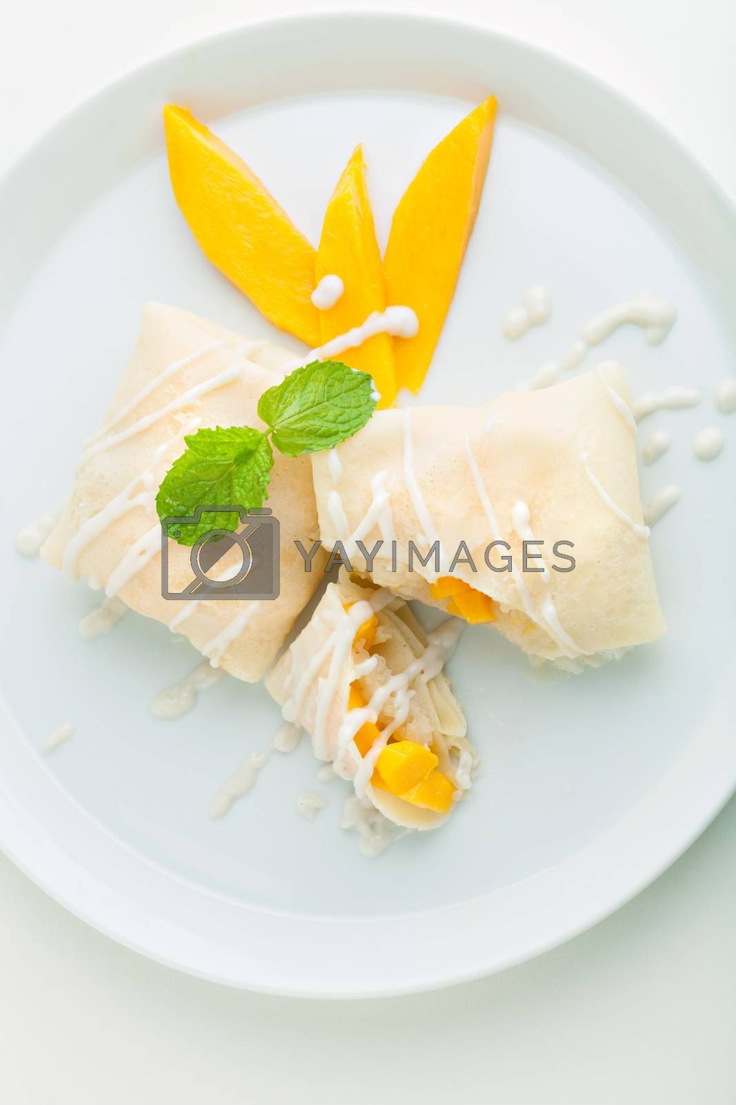 Thai style tropical dessert crepes filled with fresh mango and sticky rice. Top down overhead view.