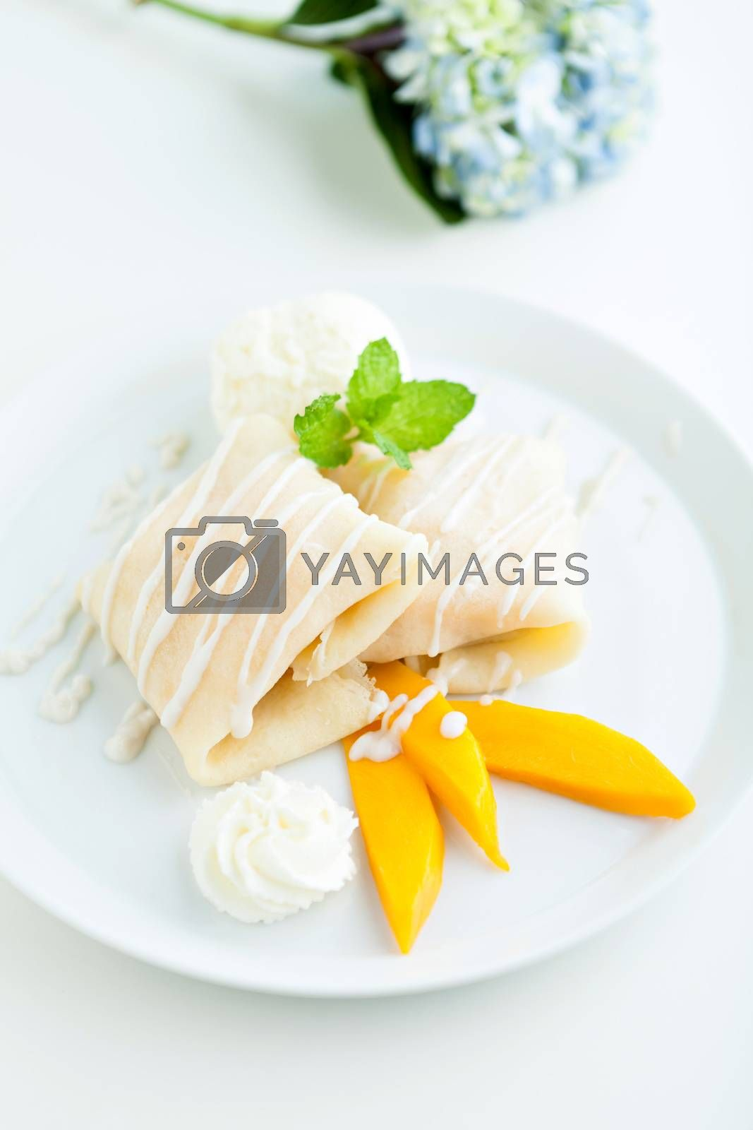 Thai style tropical dessert crepes filled with fresh mango sticky rice and a scoop of coconut ice cream. Shallow depth of field.