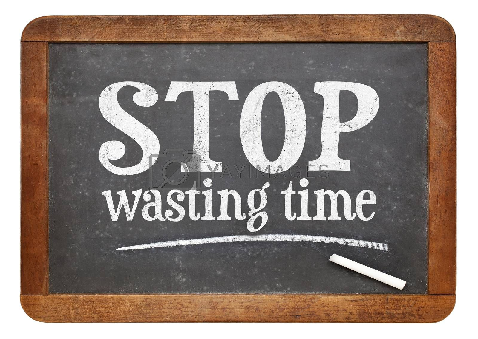 Stop wasting time sign - white chalk text on a vintage slate blackboard