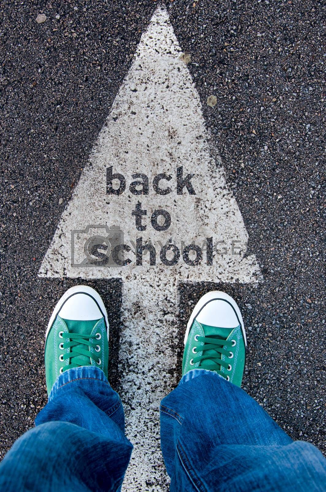 Student standing above the sign back to school