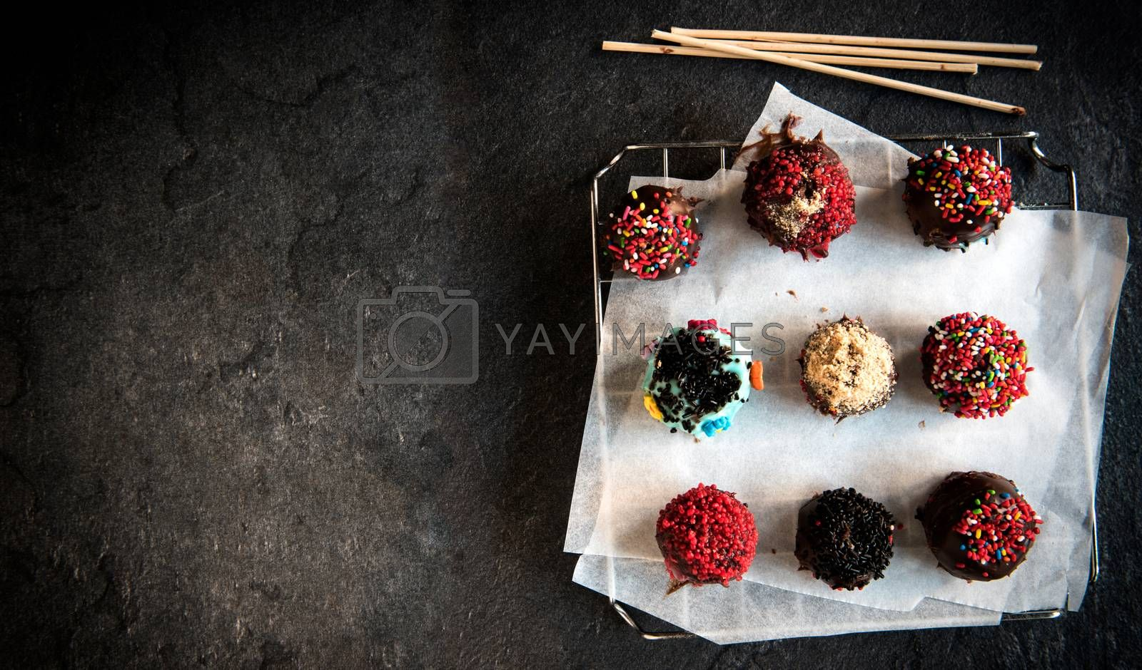 Homemade sweet chocolate cake pops on dark background with blank space