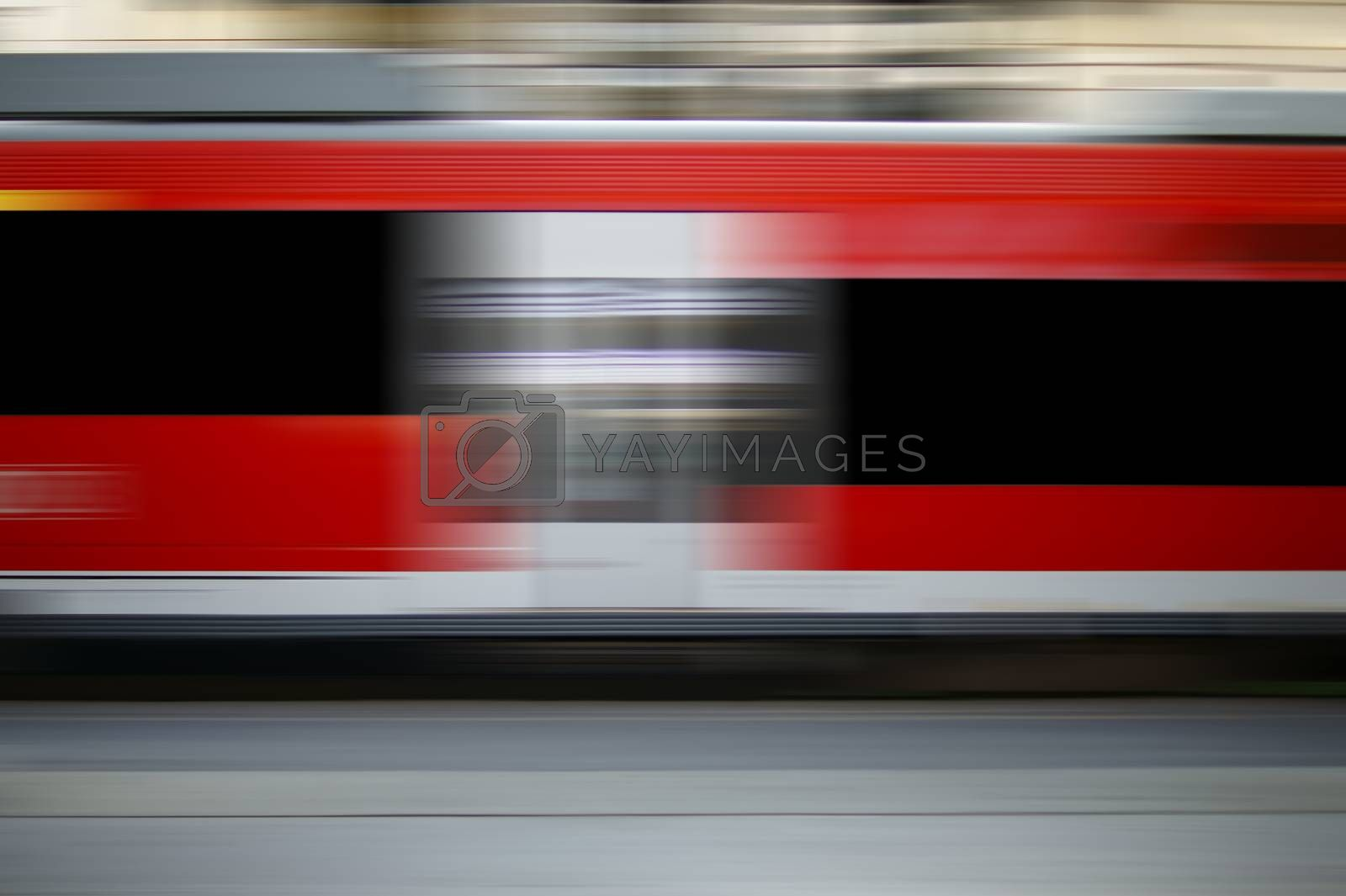 The abstract movement stripes of a passing express train at a train station.