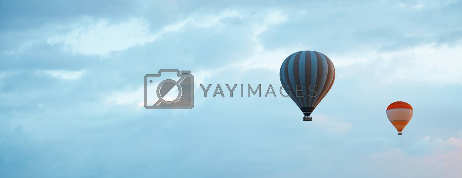 Two air balloons  in blue sky with empty space. Horizontal photo