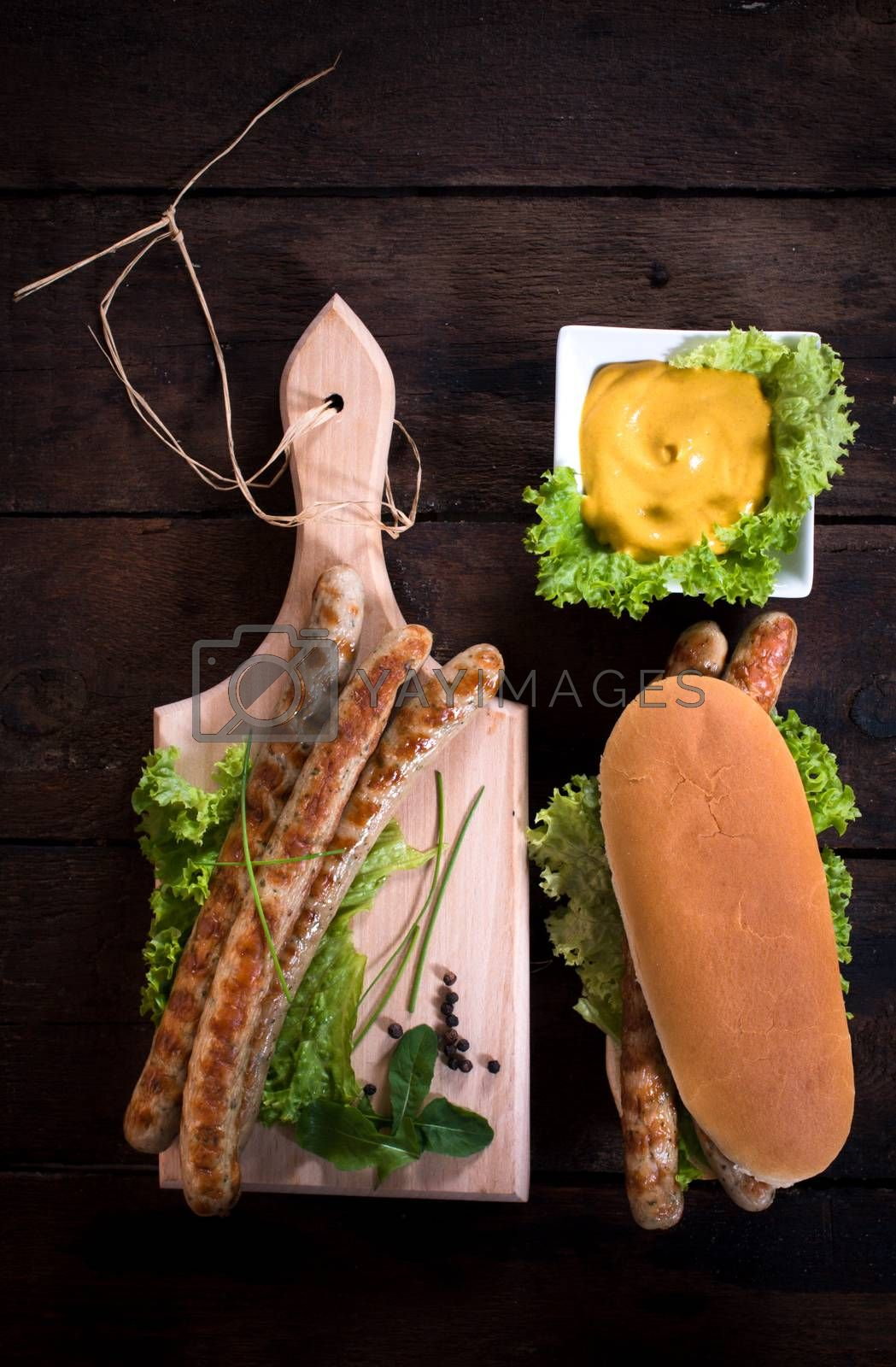Grilled sausagesand mustard on wooden background from above