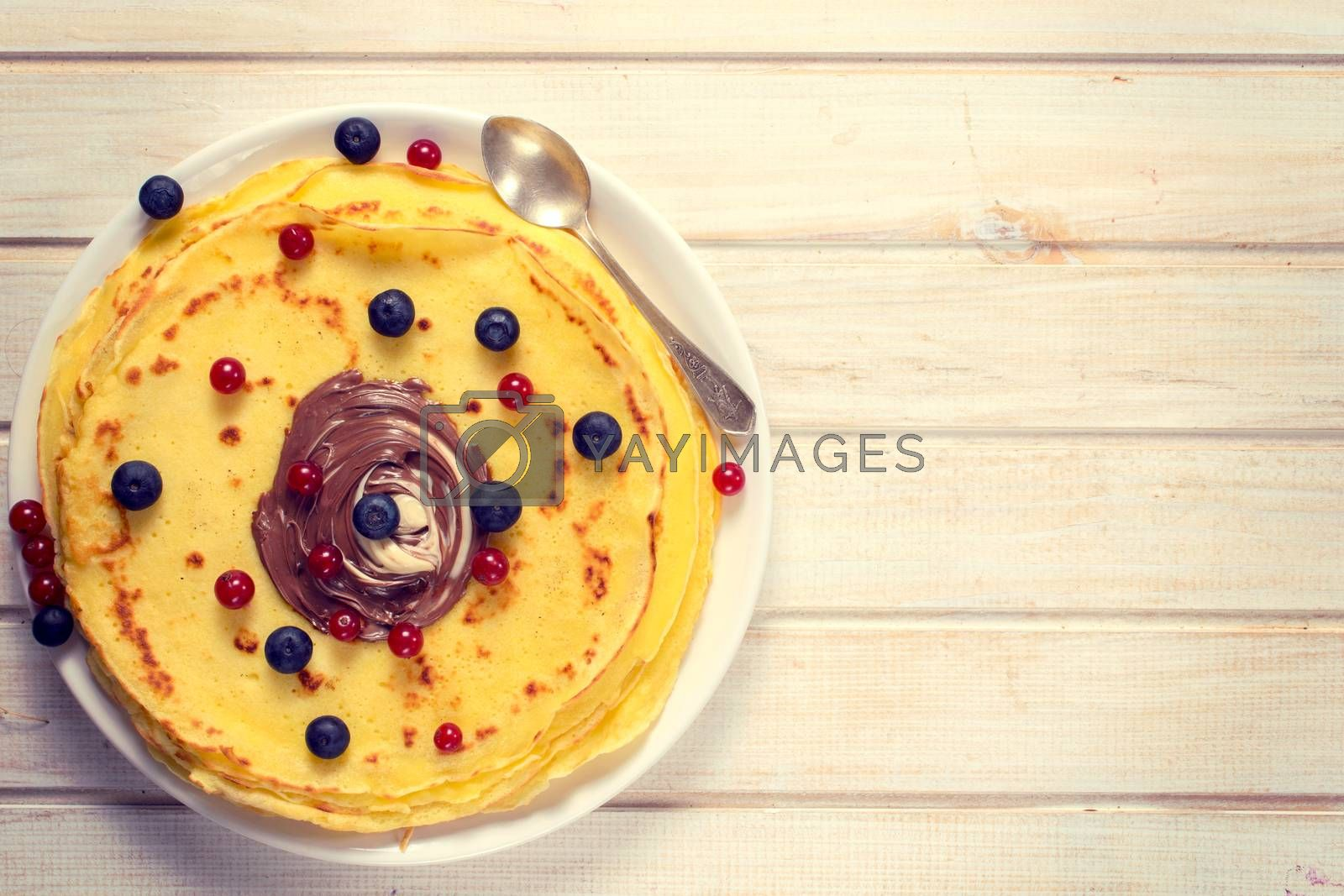 Sweet pancakes with berry fruit and chocolate cream.Blank space for text on the right side