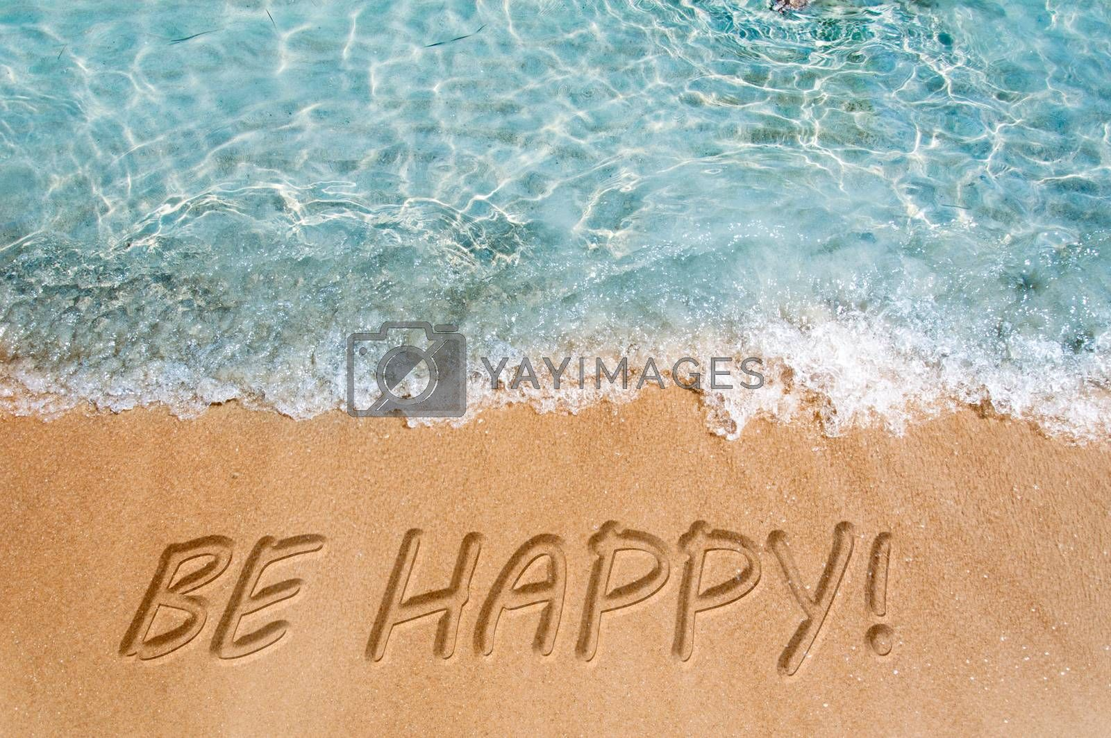 Be happy word sign on the beach sand