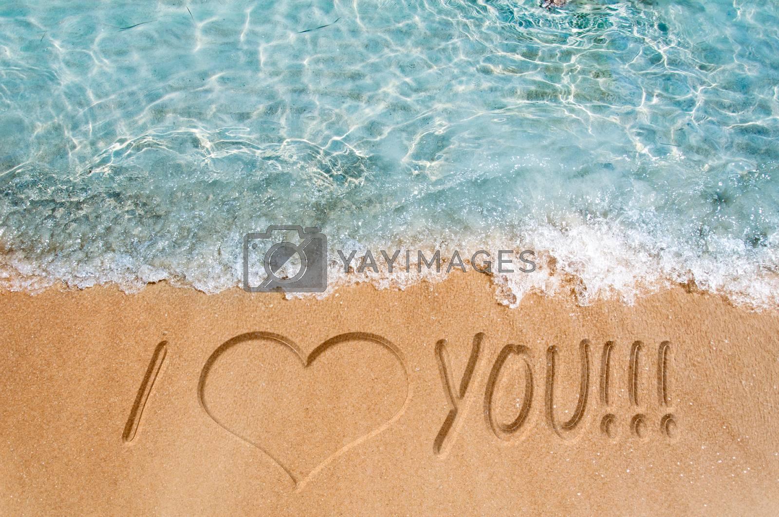 I love you word sign on the beach sand
