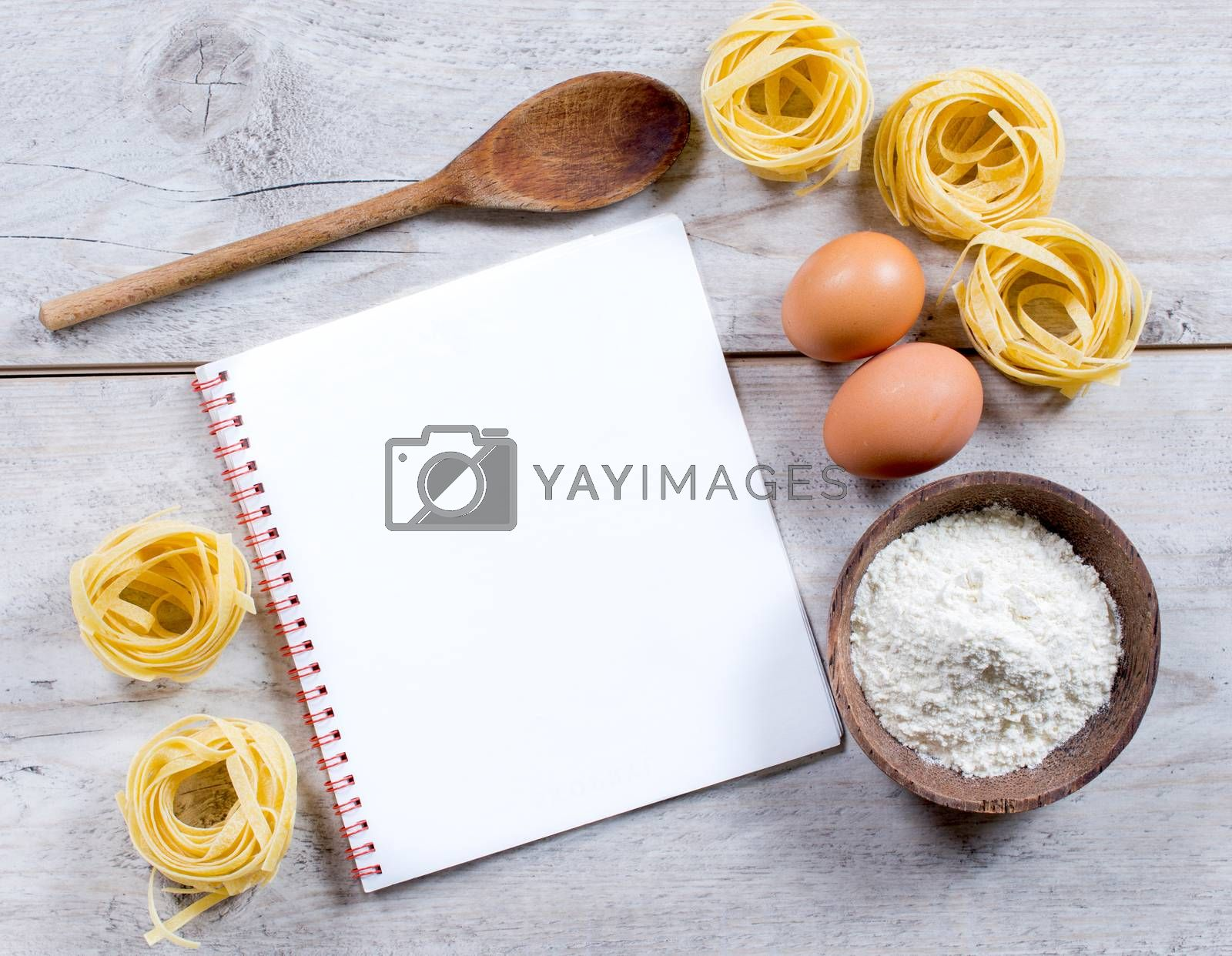 Traditional Italian tagliatelle pasta and blank book on wooden background from above,selective focus and horizontal