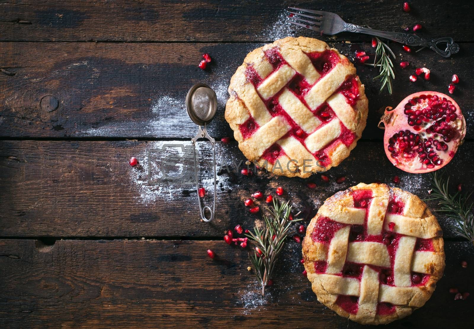 Couple of sweet tarts with pomegranate on wooden background with blank space