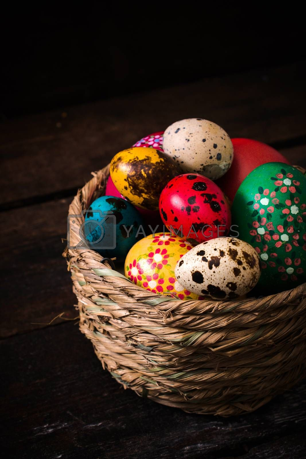Colorful Easter eggs in the basket on wooden background,selective focus
